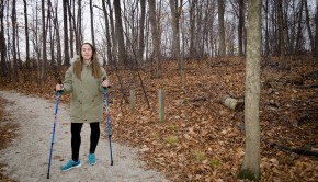 girl posing with nordic walking poles on a path in a forest with a lot of leaveson the ground during the fall