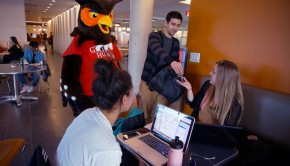 Guelph-Humber's great-horned owl mascot with three students, giving away a free USB stick as a random act of kindness, in the Guelph-Humber learning commons area.