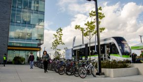 A transit car sits outside the Humber LRC building next to a row of bicycles
