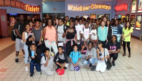 Youth group stands outside cinema posing for a photo.