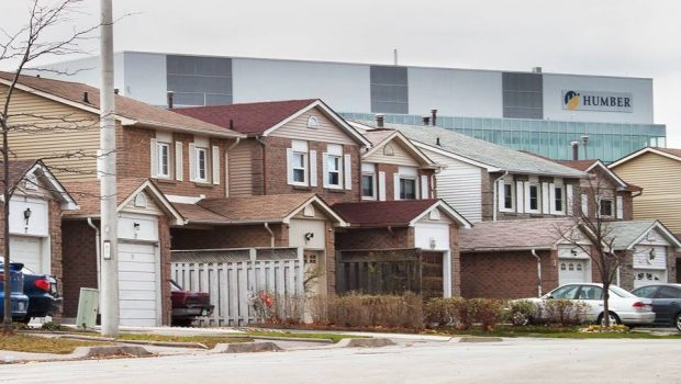 A big Humber College sign looms behind houses in the Rexdale area. If you were a resident of the area, you might perceive this as impending doom -- but students say that is just how Rexdale is.