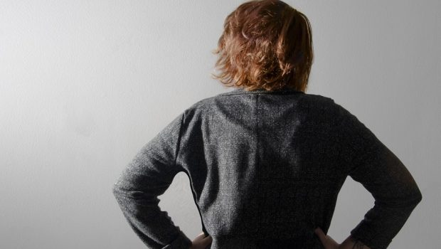 Girl in a business jacket, back towards the camera, hands on her hips.
