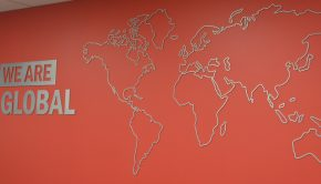 "An outline of a Word map is shown on a wall with the phrase ""we are global"" to the left of it."