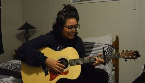 Young lady looks down while playing the guitar with a smile on her face.